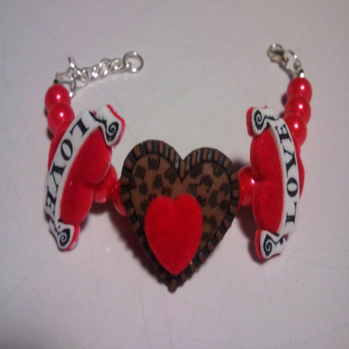 This gorgeous bracelet has two bright red felt tattoo hearts and one leopard